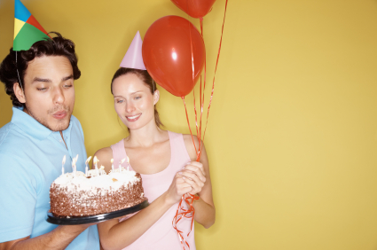 Happy young couple celebrating a birthday party with a cake against yellow background