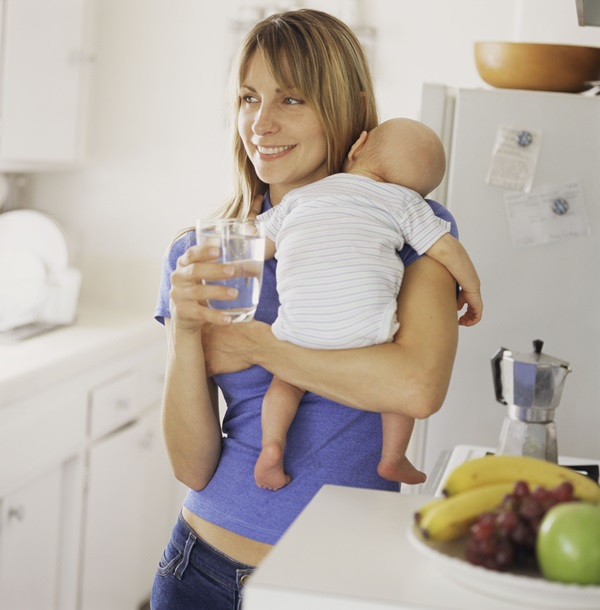 Mother holding baby in kitchen