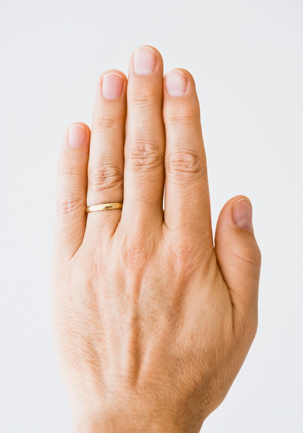 Close up of man's hand wearing wedding ring --- Image by © Tetra Images/Corbis