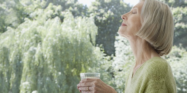 Woman relaxing outdoors with a glass of water