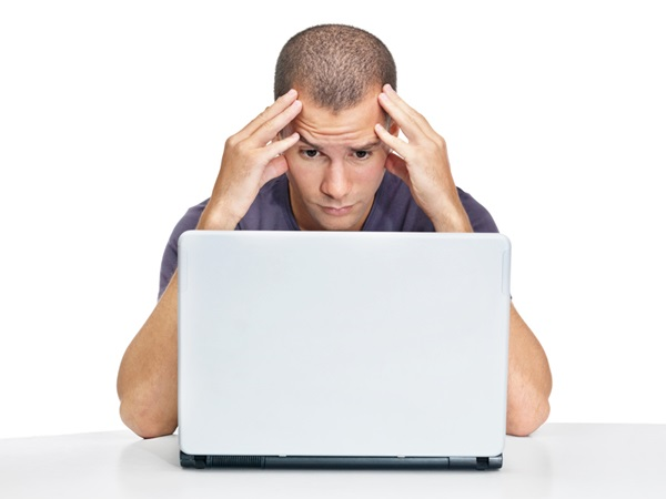 Portrait of a nervous young man looking at laptop against white background